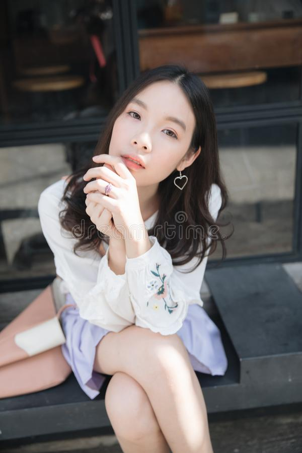 Portrait of asian girl with white shirt and skirt sitting and looking in outdoor nature vintage film style. In close up stock image