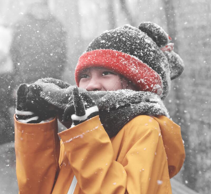 Portrait of Asian girl with winter clothing fashion with snow falling in the background stock photo