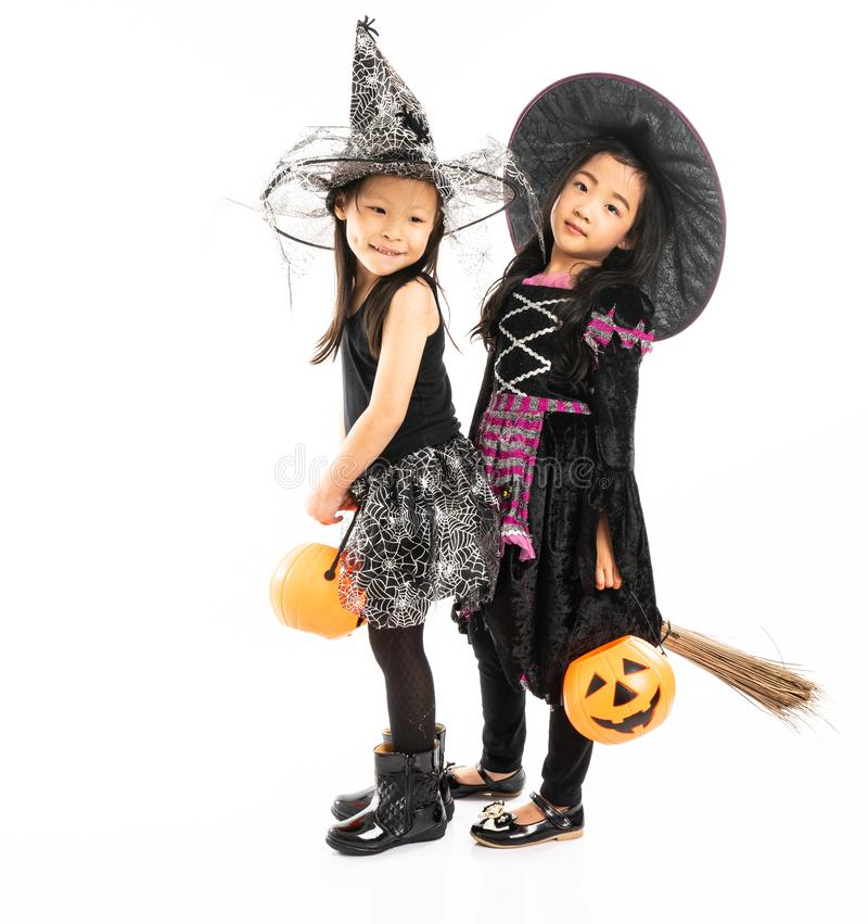 Portrait Asian girls in Halloween costume riding the broom together and holind the pumpkin with isolated background royalty free stock photography