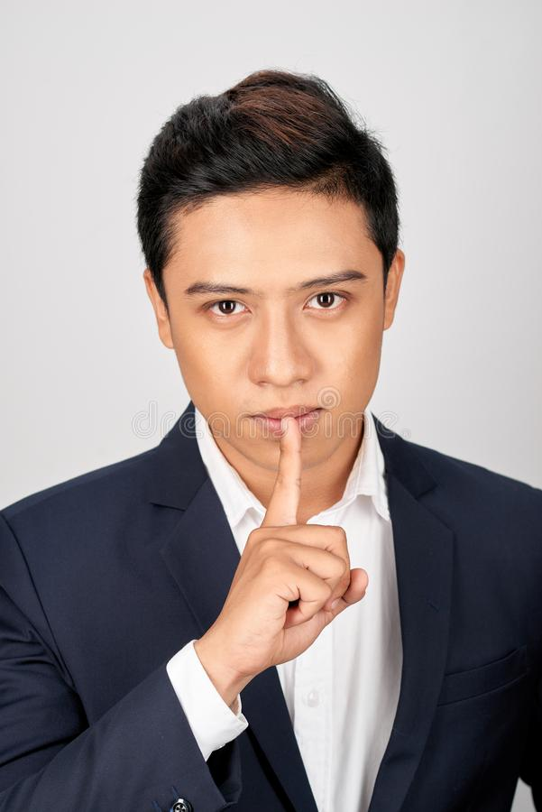 Portrait of Asian handsome businessman dressed in suit showing silence gesture and looking at camera isolated over white royalty free stock photos