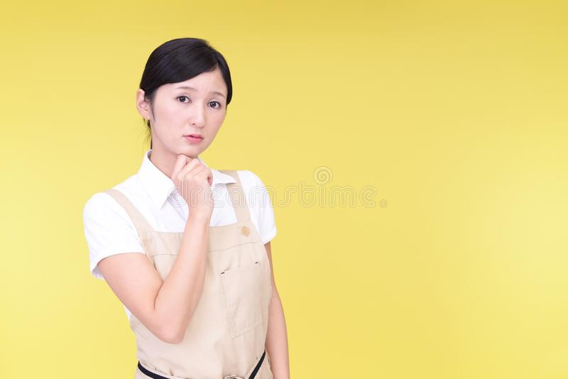 Uneasy Asian woman in apron stock photo
