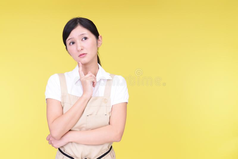 Uneasy Asian woman in apron stock image