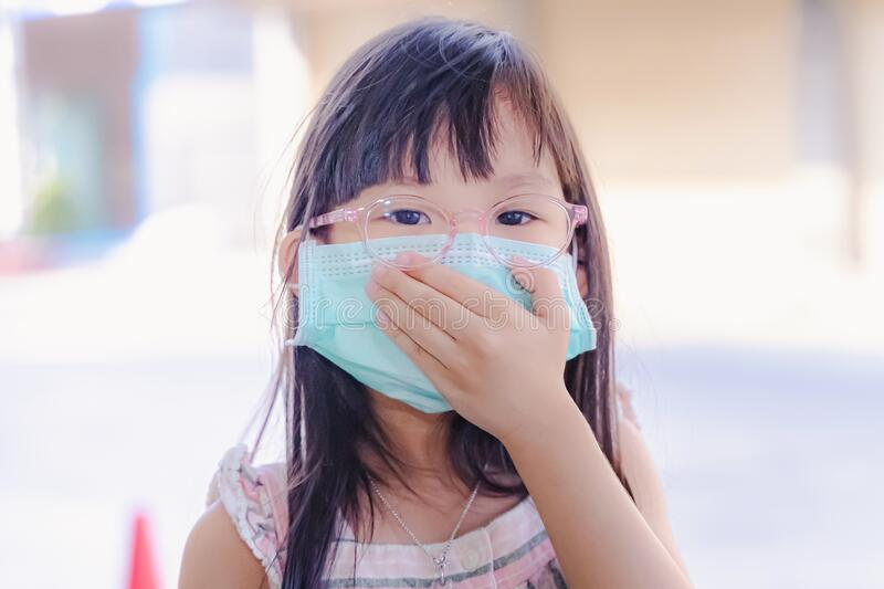 Portrait Asian kid wearing medical mask. A girl wearing mouth mask against air smog pollution. Concept of corona quarantine. Or covid-19.Protection against and stock images