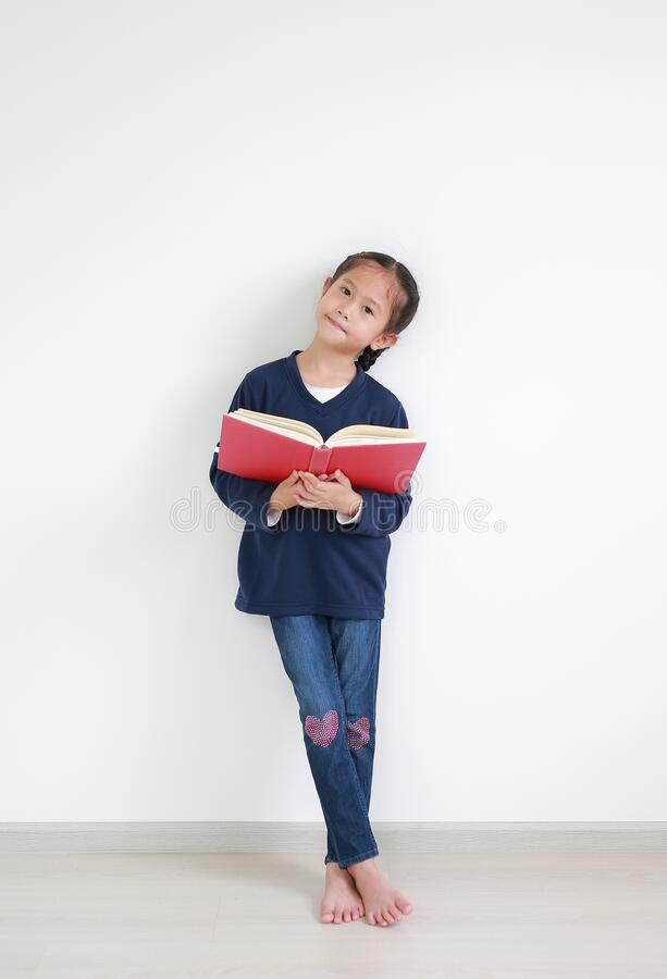 Free Portrait Asian Little Child Girl In Casual School Uniform Reading A Book And Standing Against White Wall In The Room Royalty Free Stock Image - 196959716
