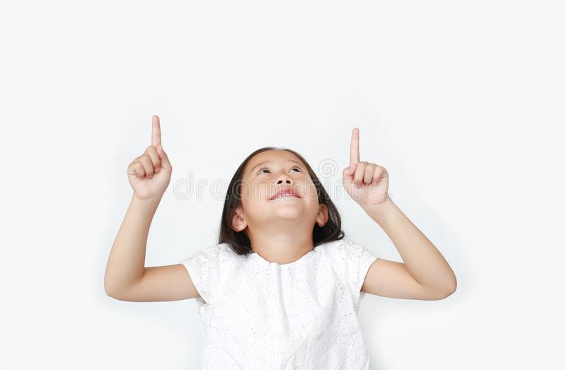 Portrait of Asian little child girl pointing two forefinger up and looking above isolated over white background royalty free stock photography