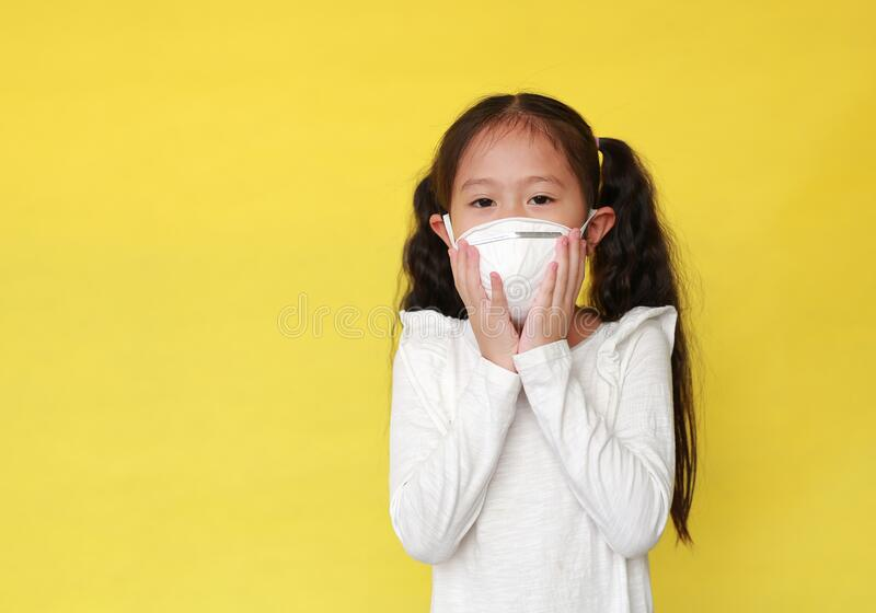 Portrait of asian little child girl wearing a protection mask for against air pollution isolated on yellow background. Kid with royalty free stock photography