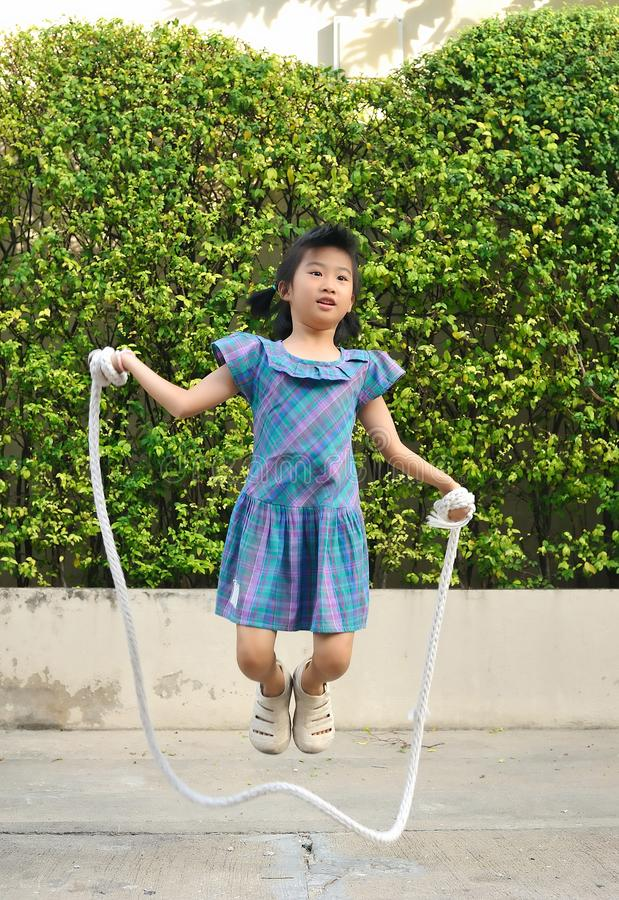 Portrait of asian little girl jumping handmade rope among swing in the park. royalty free stock photos