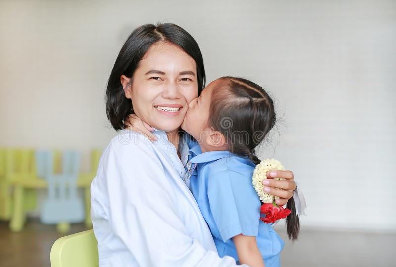 Portrait of Asian little girl kissing her happy mom and hugging on Mother`s day in thailand. Kid Pay respect and give Thai traditional jasmine garland to stock photo