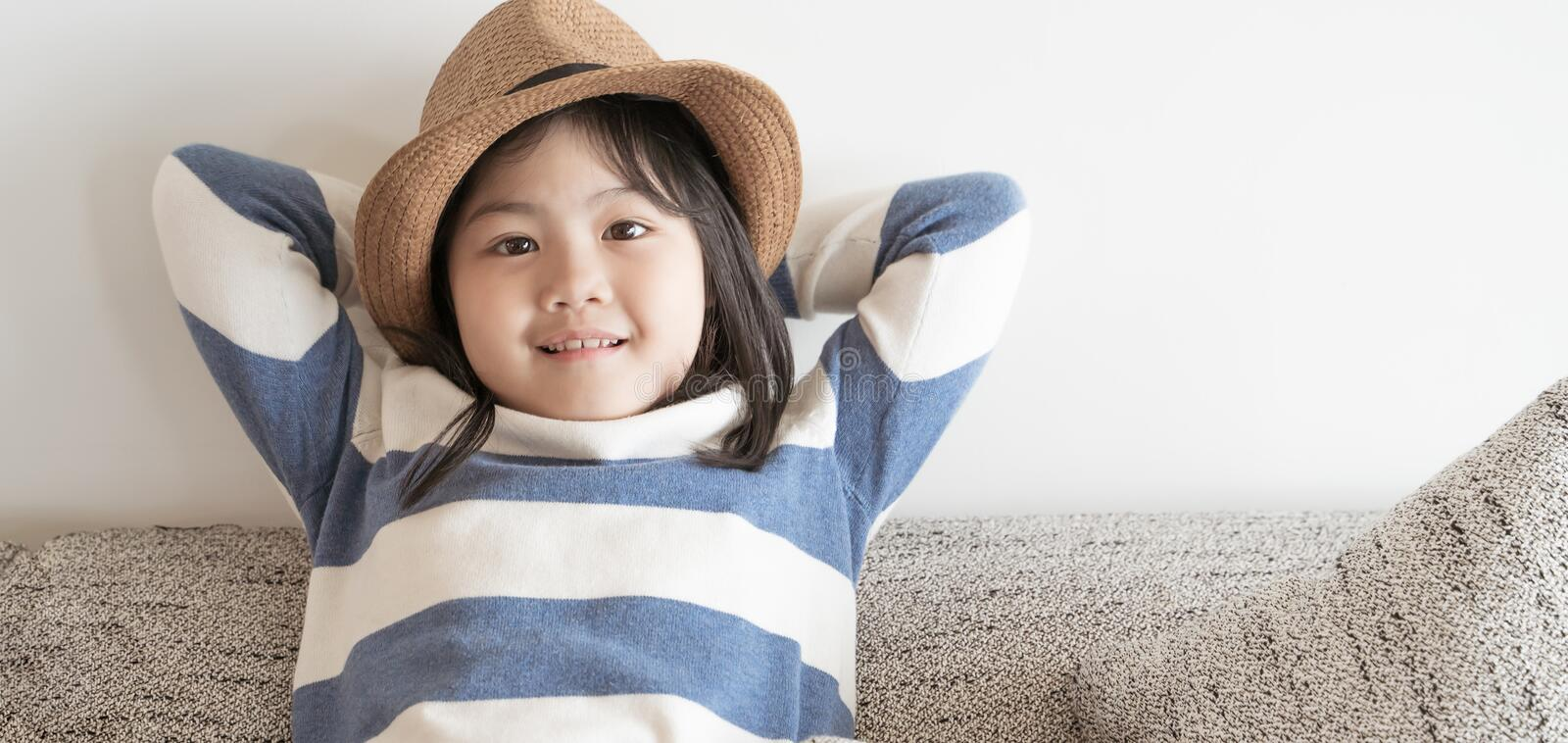 Portrait asian little girl sit on sofa and wear hat stock photo