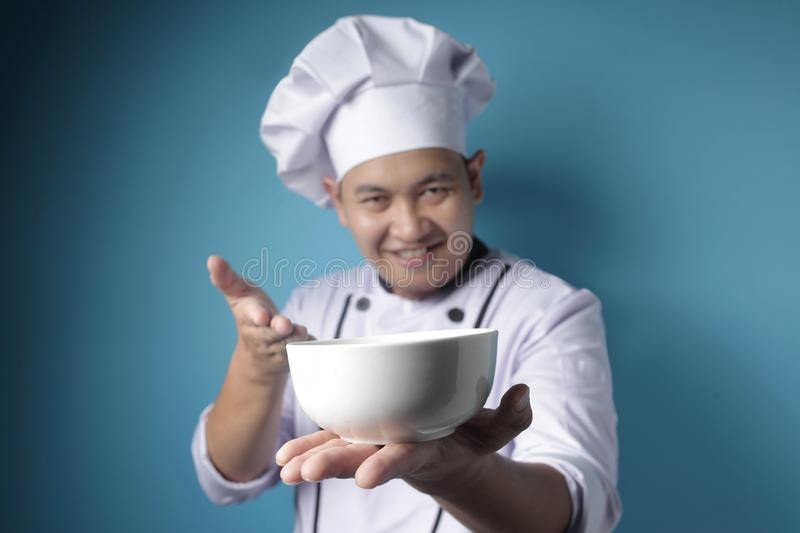 Asian Male Chef Shows Empty White Bowl, Presenting Something, Copy Space royalty free stock images