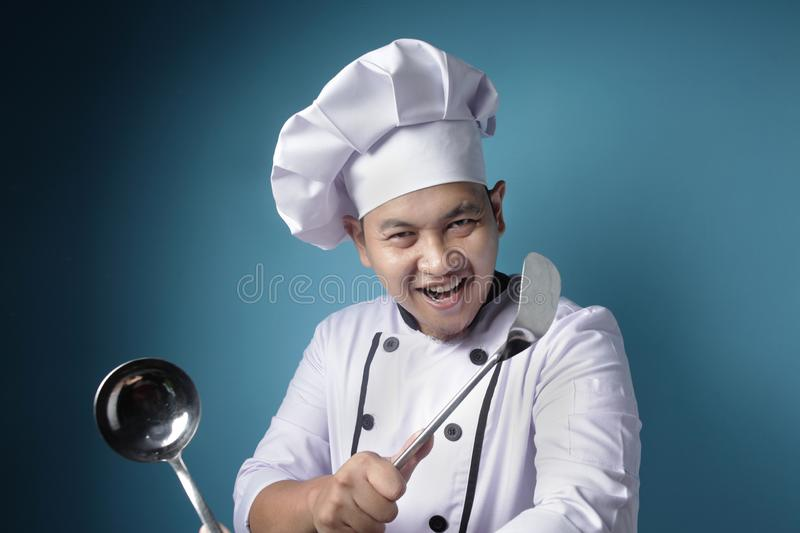 Kungfu Chef, Male Asian Chef Holding Ladle and Spatula, Ready to Cook royalty free stock photo