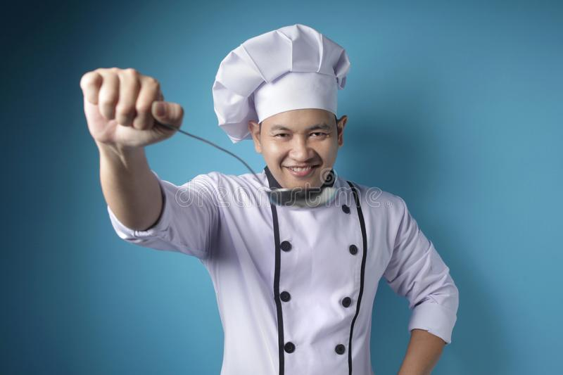 Asian Male Chef Making Soup, Chef Holding Kitchen Tool Ladle royalty free stock photos