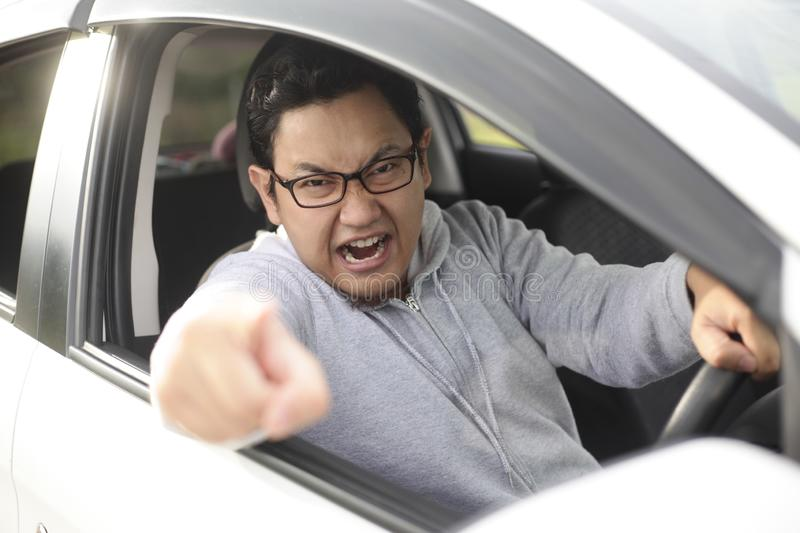 Angry Asian Male Driver, Screaming Pointing From His Car stock photography
