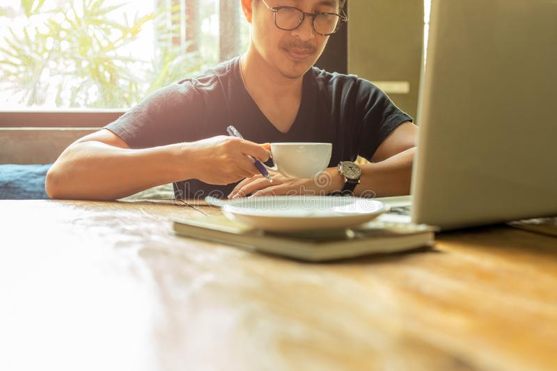 Portrait asian man with glasses having coffee break working with laptop. royalty free stock photography