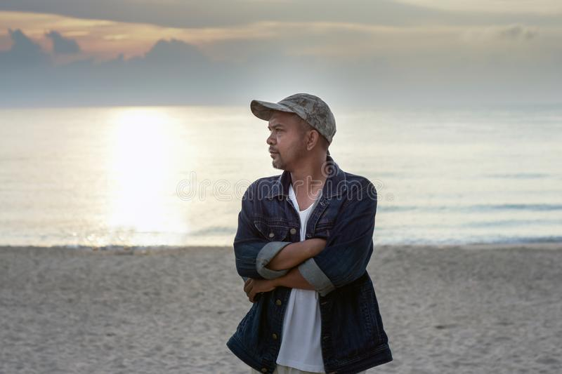 Asian man wearing cap standing arms crossed with sea background. Portrait of Asian man wearing cap standing arms crossed with sea background stock photography
