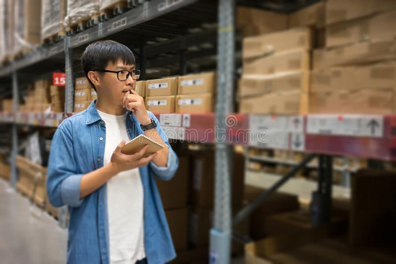 Portrait Asian men, staff, product counting Warehouse Control Manager Standing, counting and inspecting products in the warehouse stock image