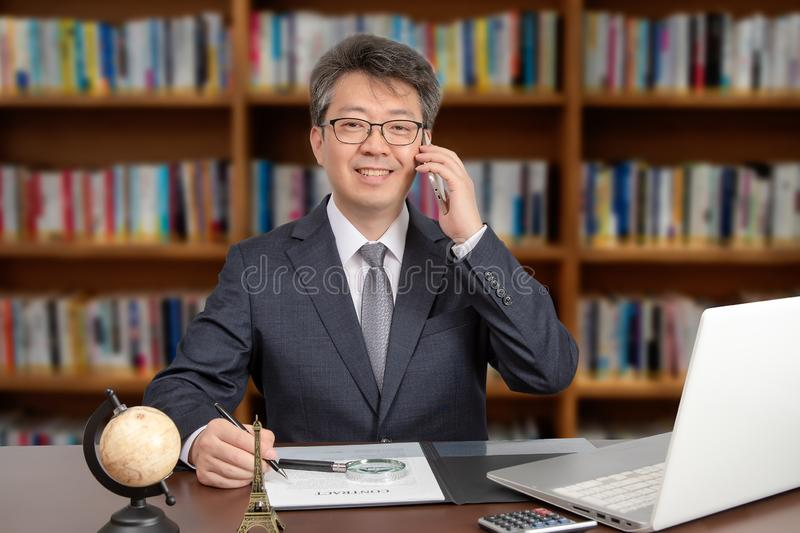 A portrait of an Asian middle-aged male businessman sitting at a desk, smiling and talking on the phone royalty free stock photo