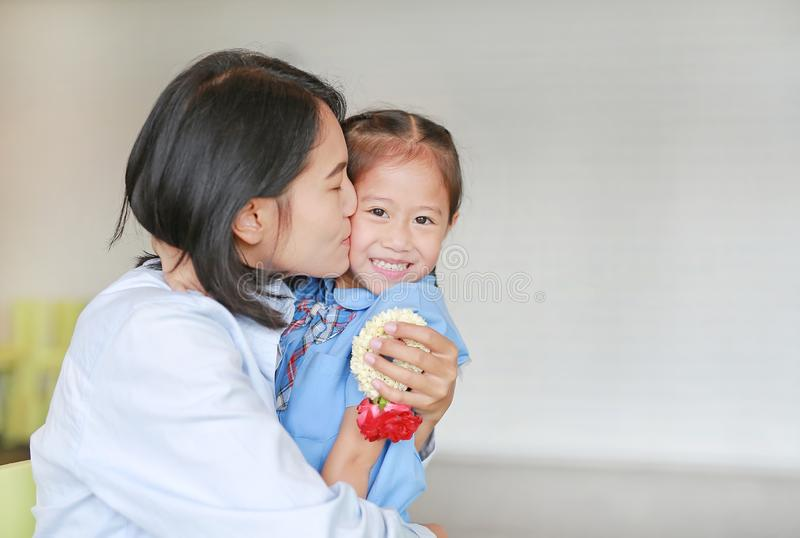 Portrait of Asian mom kissing and hugging her daughter on Mother`s day in thailand. Little child girl Pay respect and give Thai traditional jasmine garland to royalty free stock images