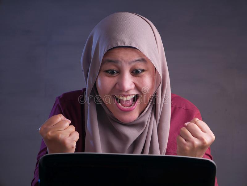 Muslim Lady Shows Winning Gesture, Receiving Good News on Her Email royalty free stock photography