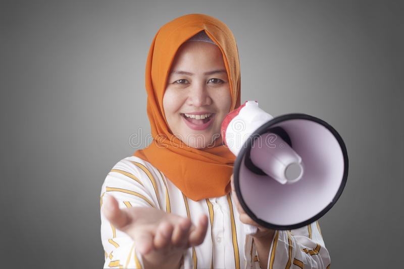 Muslim Businesswoman Calling or Offering Something with Megaphone, Advertising Marketing Concept. Portrait of Asian muslim woman calling or offering something stock photos