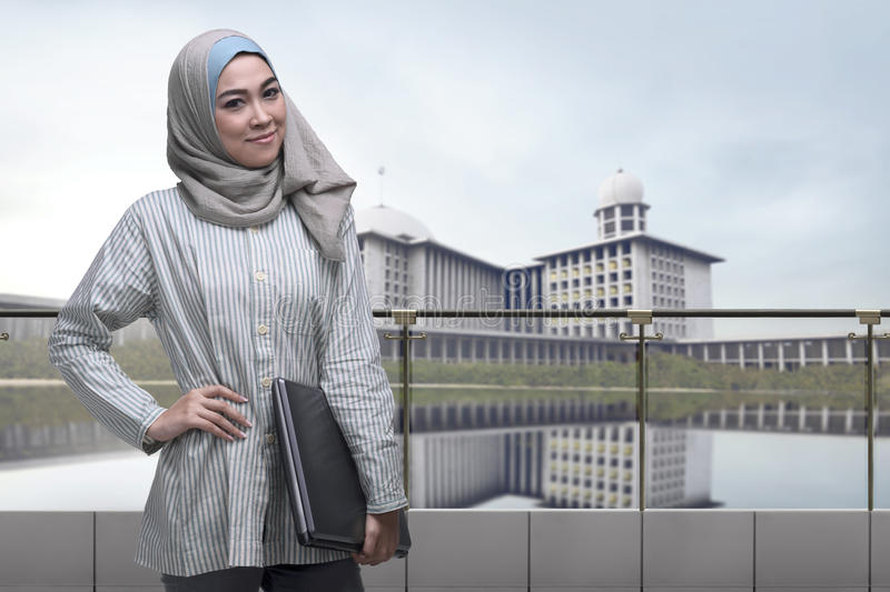 Portrait of asian muslim woman with hijab holding laptop. With mosque background stock photo