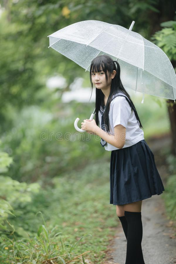 Portrait of Asian school girl walking with umbrella at nature walkway on raining royalty free stock images