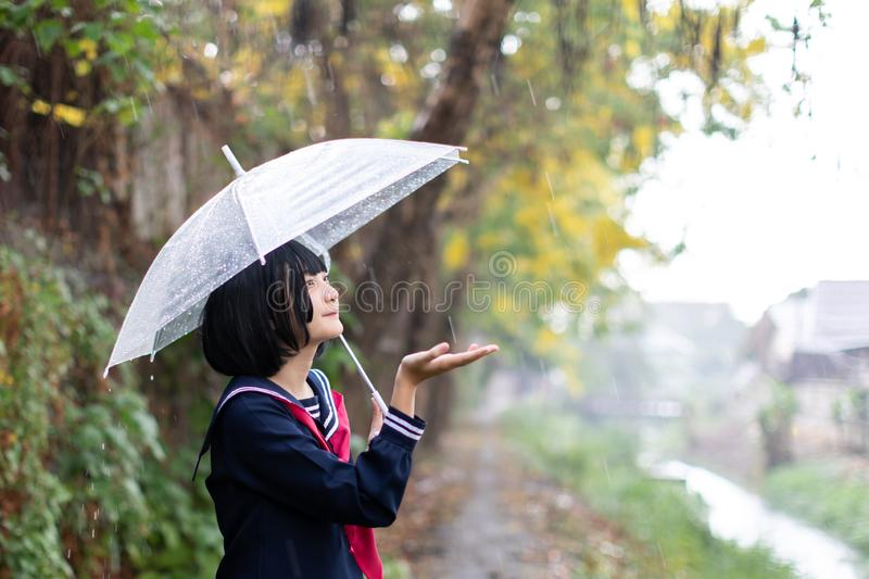 Portrait of Asian school girl walking with umbrella stock photo