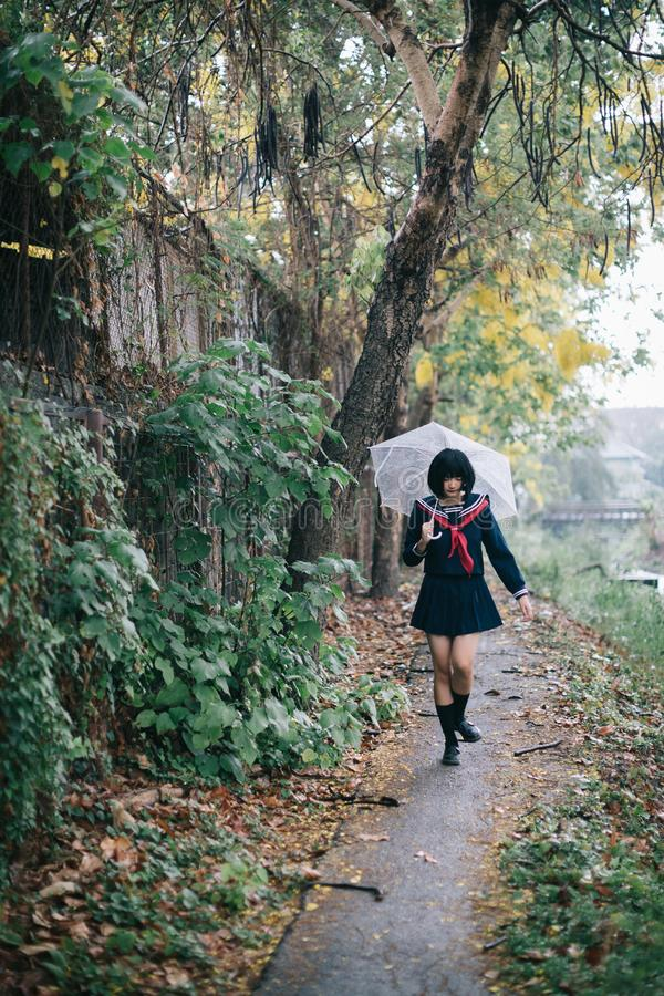 Portrait of Asian school girl walking with umbrella royalty free stock images