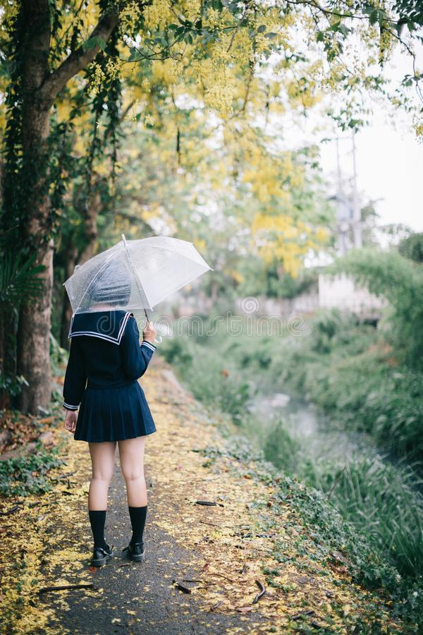Portrait of Asian school girl walking with umbrella royalty free stock photos
