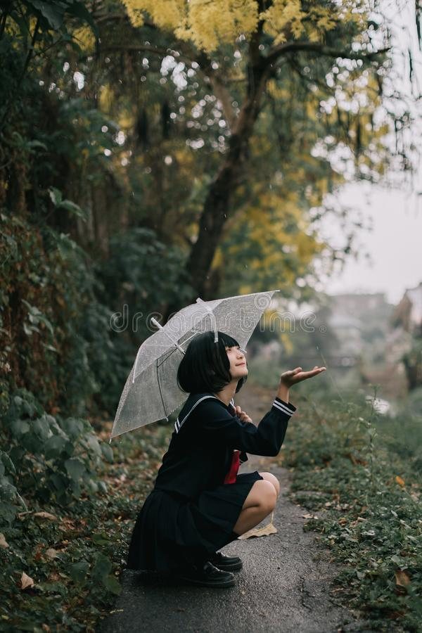 Portrait of Asian school girl walking with umbrella at nature walkway stock images