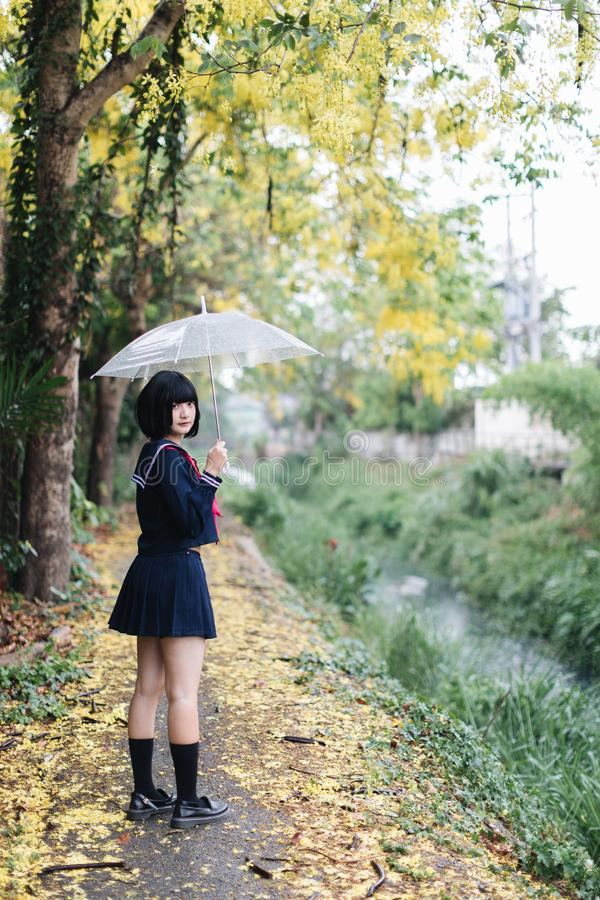 Portrait of Asian school girl walking with umbrella royalty free stock image