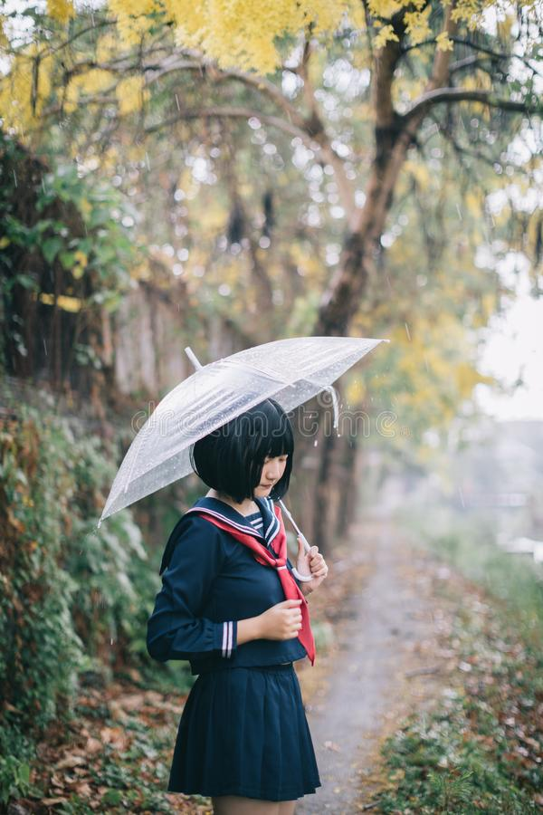 Portrait of Asian school girl walking with umbrella stock photos