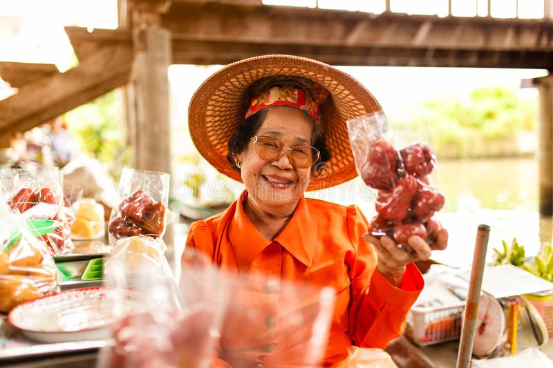 Portrait asian senior female smiling and selling many fruit at Damnoen Saduak floating market in Ratchaburi near Bangkok stock images