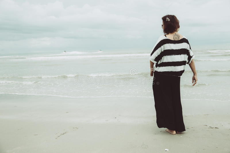 Portrait asian single tattoo hipster indy women lonely stand alone on the beach royalty free stock image