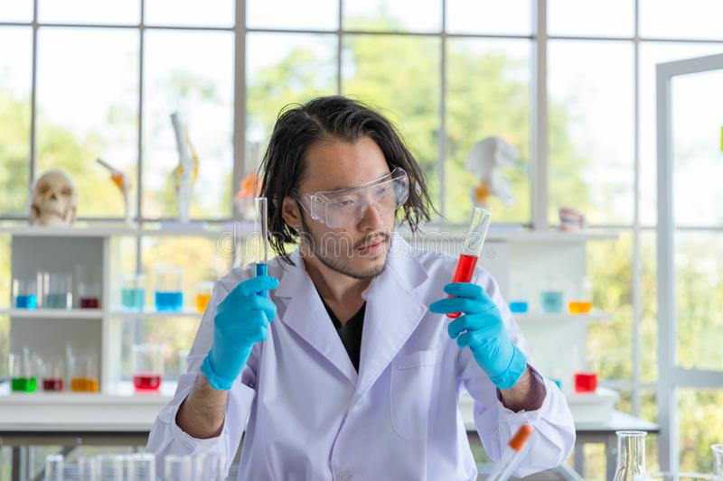 The Portrait of the Asian smart man scientist is holding two test tubes. In research laboratory stock photo