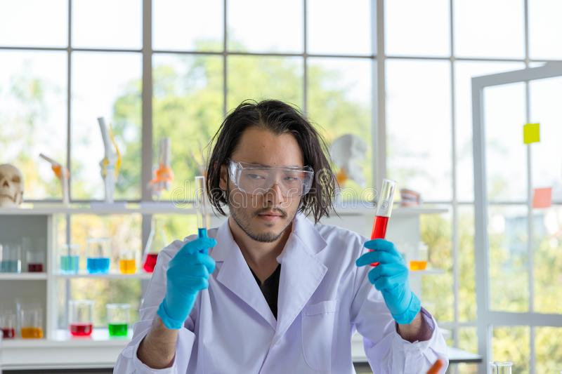 The Portrait of the Asian smart man scientist is holding two test tubes. In research laboratory royalty free stock photo