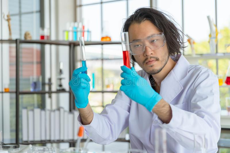 The Portrait of the Asian smart man scientist is holding two test tubes. In research laboratory royalty free stock photos