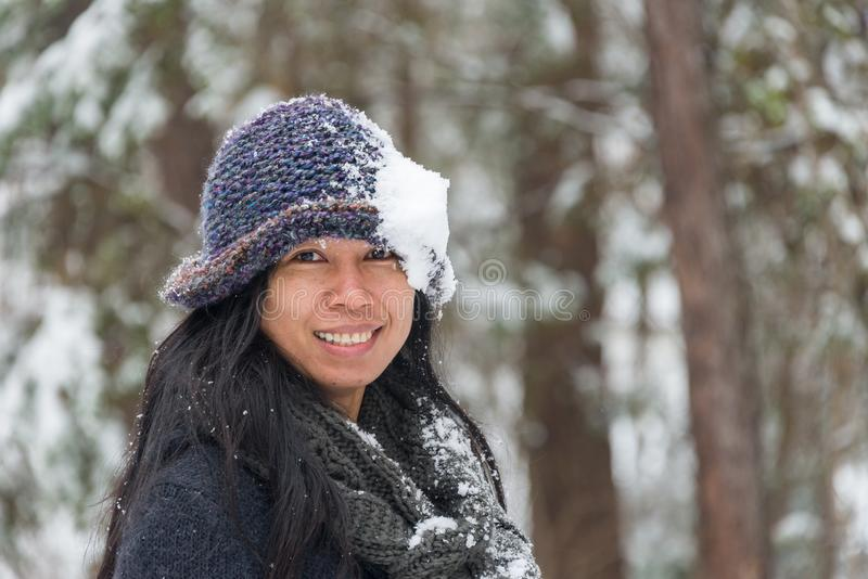 Portrait of Asian woman with hat. Portrait of Asian woman with snow covered hat and smiling with trees in the background royalty free stock images