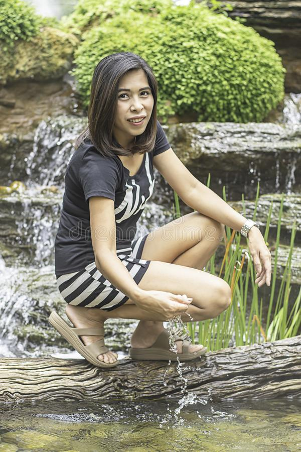 The portrait of Asian woman is playing with water from a waterfall royalty free stock image