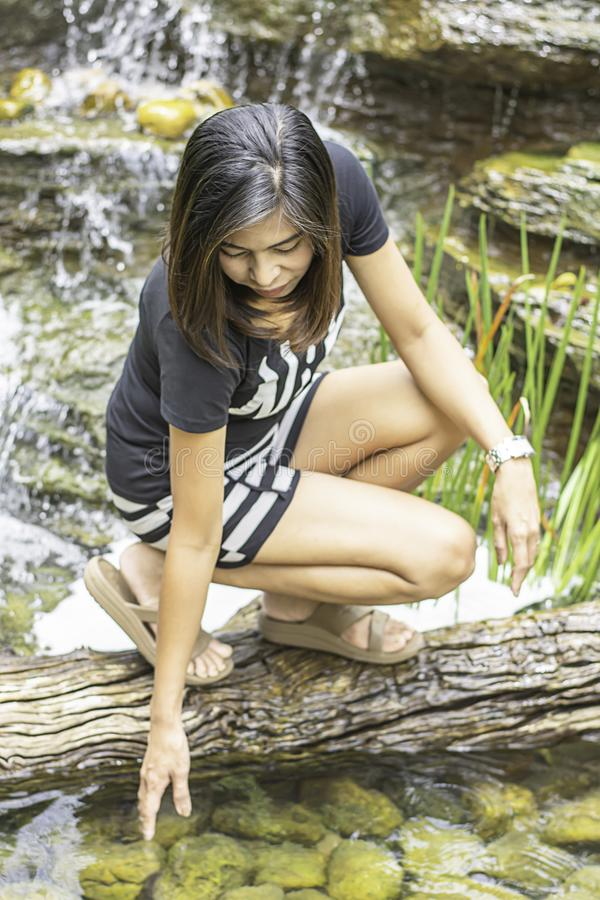 The portrait of Asian woman is playing with water from a waterfall royalty free stock photo