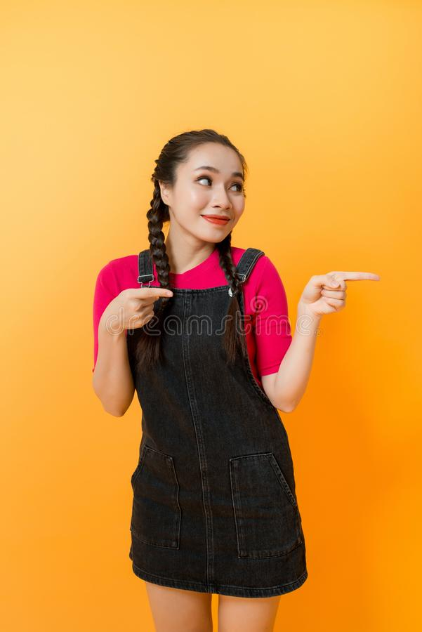 Portrait of Asian woman pointing at something on color background royalty free stock photography