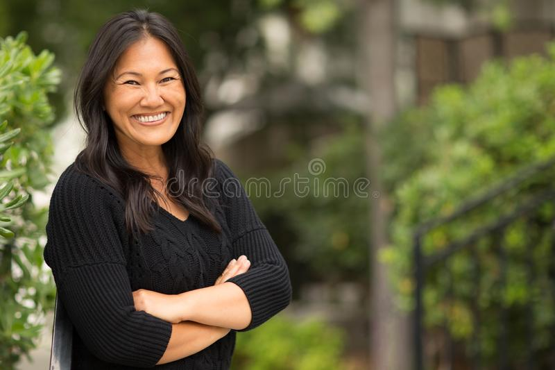Portrait of an Asian woman sitting outside. stock photography