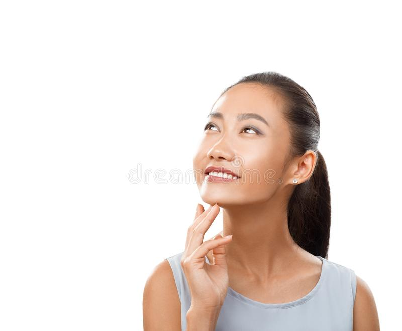Portrait of Asian woman with smile looking up thoughtfully. Happy girl close-up with fingers near chin and with her head slightly deflected backwards. Smiling royalty free stock images