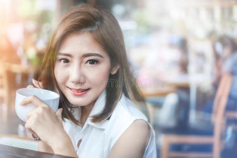 Portrait of asian woman smiling and holding cup of coffee. With glass window reflecting street city blur bokeh stock images