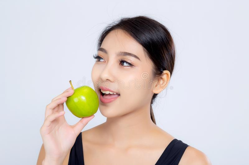 Portrait asian woman smiling holding and eating green apple fruit and beautiful body diet with fit isolated on white background. Girl weight slim with royalty free stock photo