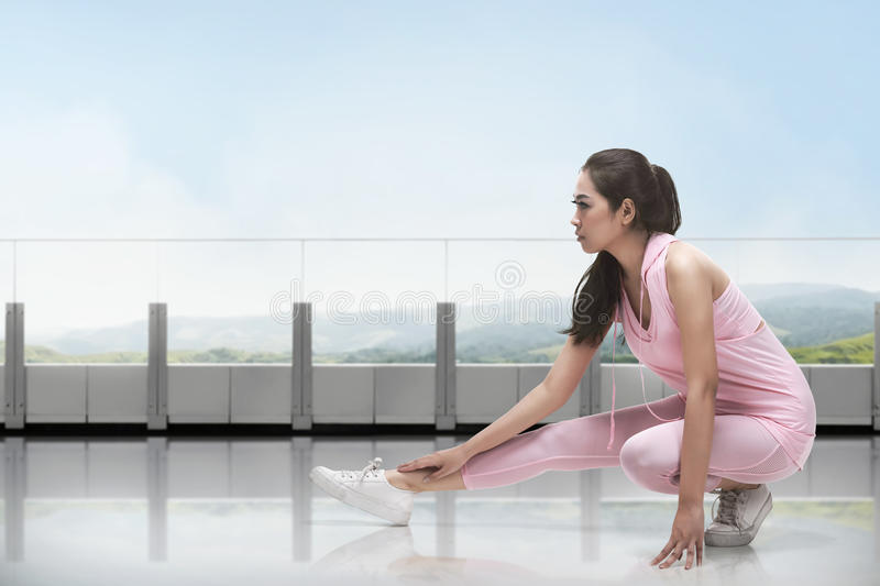 Portrait of asian woman in sportswear doing stretching while kneeling. In front of window at gym royalty free stock photography