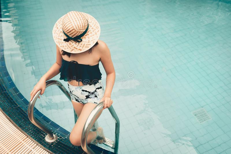 Portrait of asian woman standing posing beside swimming pool while holding grab bar ladder royalty free stock image