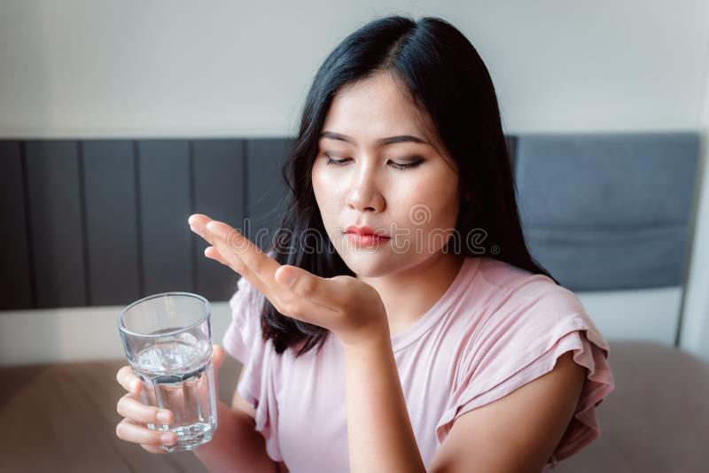 Portrait of Asian Woman Taking Medicine Pill While Holding a Glass of Water and Sitting on Bedroom., Medication Pharmacy Illness T royalty free stock photos