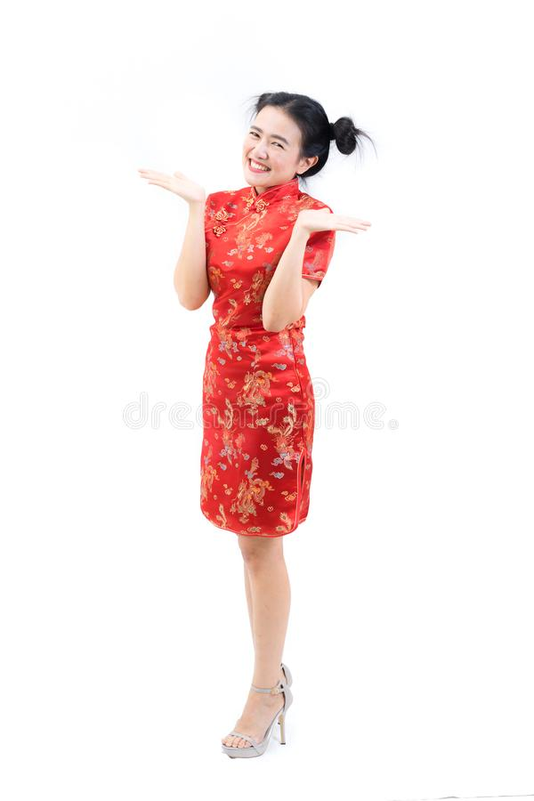 Portrait of asian woman in traditional chinese long dress, cheongsam, black hair, hands presenting her face for Chinese New Year royalty free stock photography