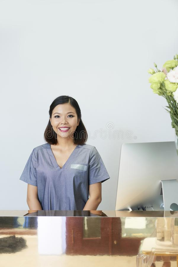 Woman in wellness center. Portrait of Asian woman in uniform standing at her workplace at reception smiling in wellness center stock photography